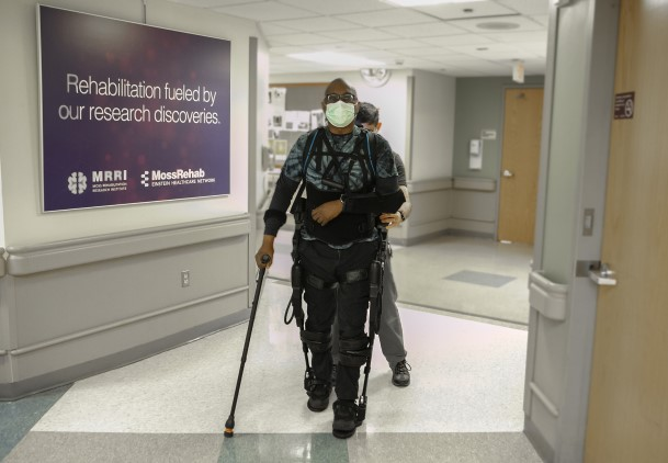 A patient with one arm in a sling and a crutch in the other walking with the assistance of an exoskeleton and physical therapist.
