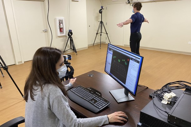 A male research participant wearing sensors stands in the middle of a room with arms stretched out wide while a female researcher monitors data on a computer screen.