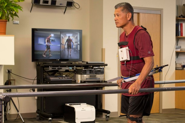 A male patient wearing sensors walks down a runway while holding onto guard rails.
