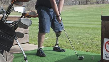 Man with a prosthetic leg swinging a golf club.