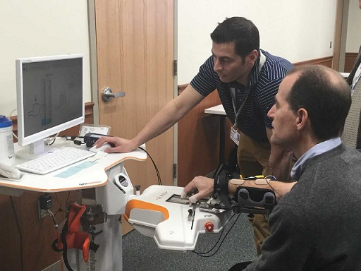 Therapist giving a demonstration of robotic device to a visitor.