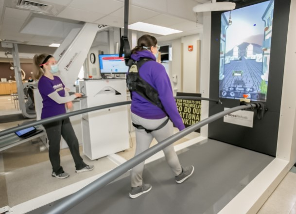 A woman being held up by a harness walks on a large treadmill while watching a LCD screen