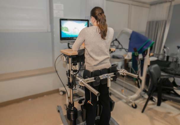A patient strapped to device which helps her stand and balance.
