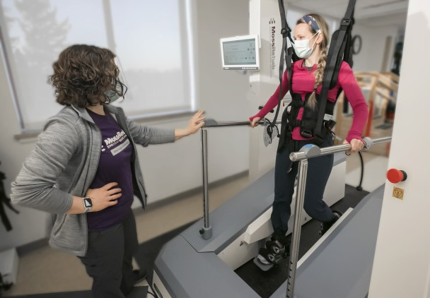 A physical therapist standing next to a patient who is strapped into a harness and stepping device.